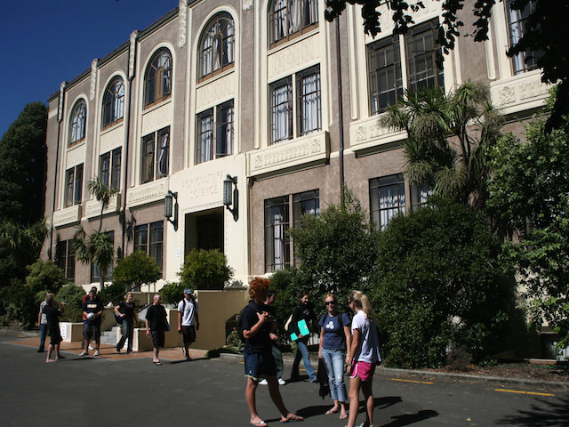 A group of students stand together outside a building on Massey University- Palmerston North campus