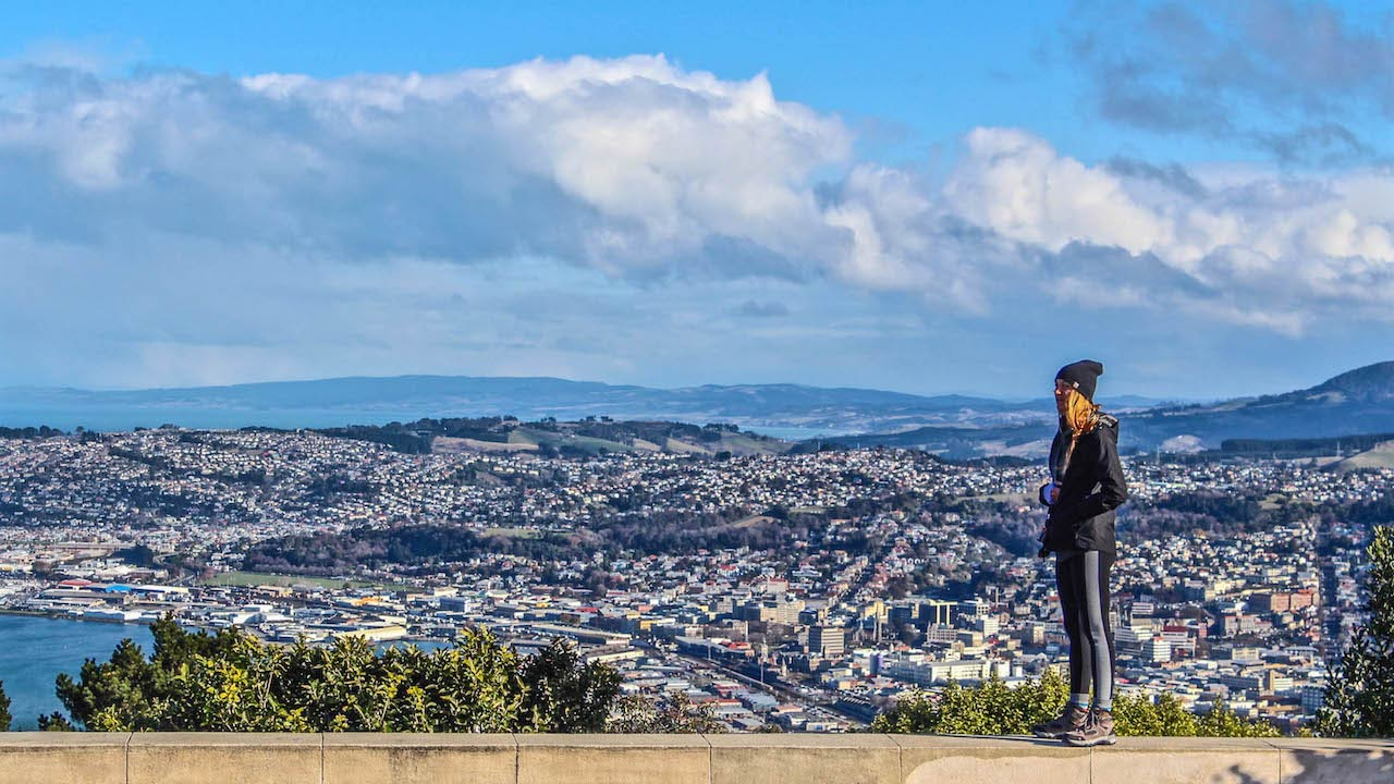 A woman stands on a platform looking out over the city of Dunedin, New Zealand