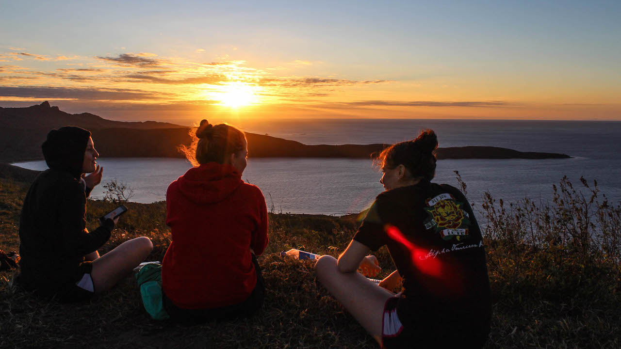 Two women sit looking out at a beautiful sunset over a lake near Otago, New Zealand