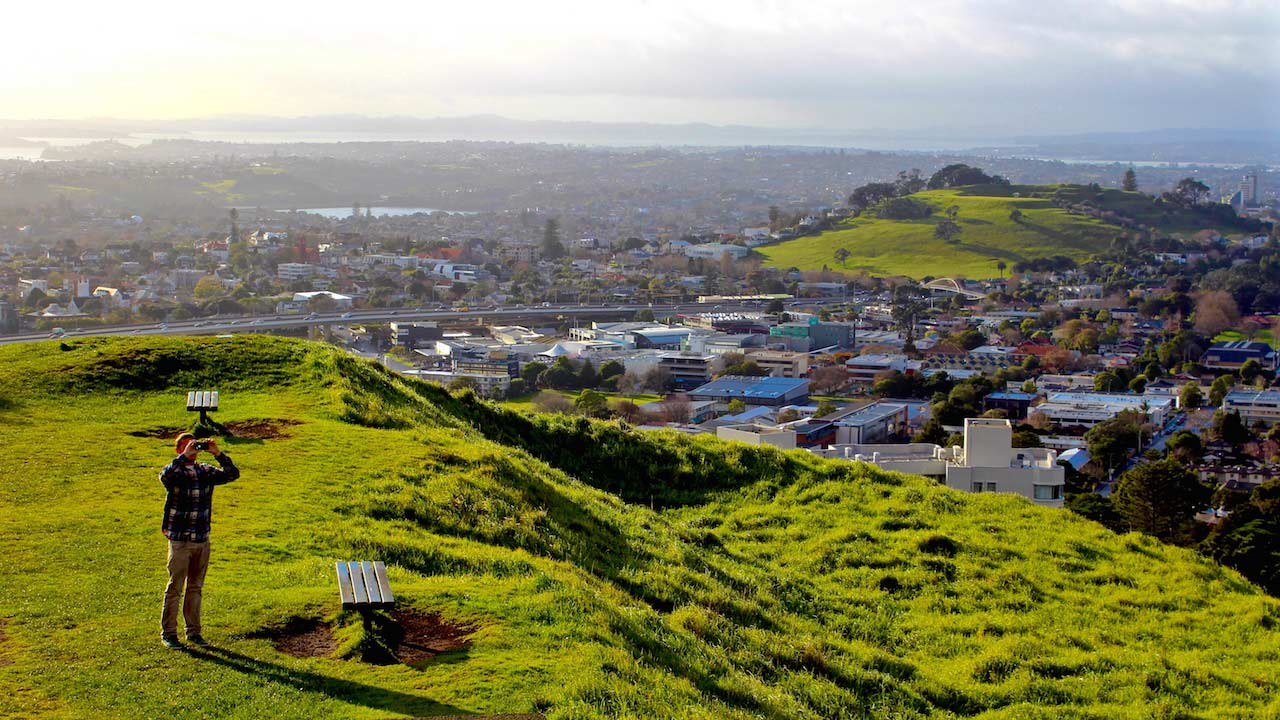 A man stands on a grassy hill overlooking Auckland and looks at the sky with binoculars