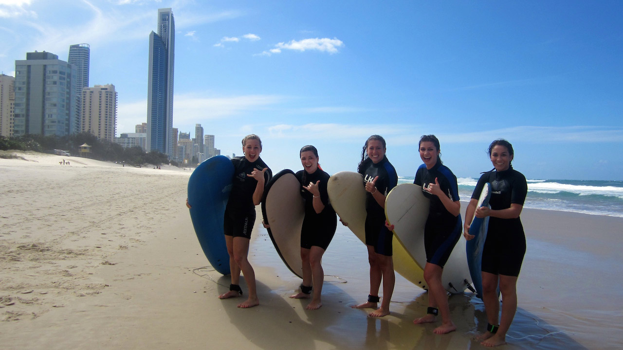 Five students stand in wetsuits with surfboards on the beach