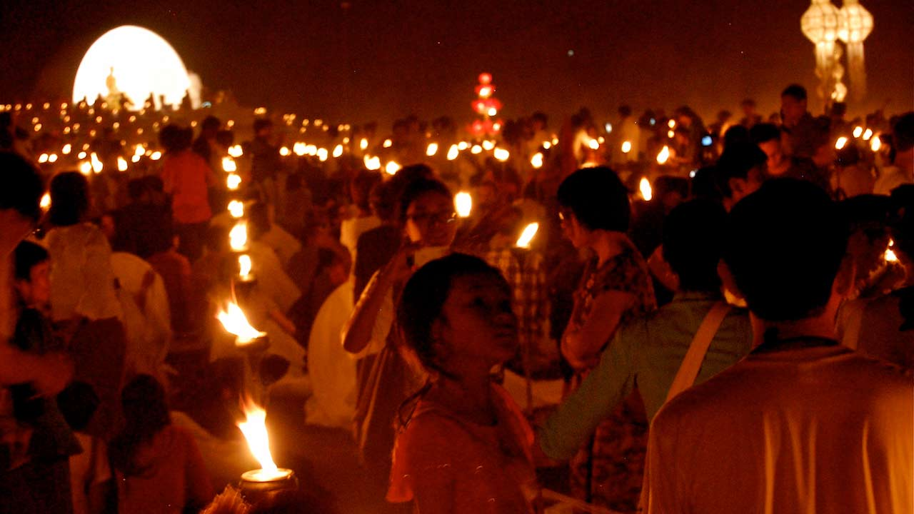 Crowds of people hold lit candles for an evening ceremony in Chiang Mai