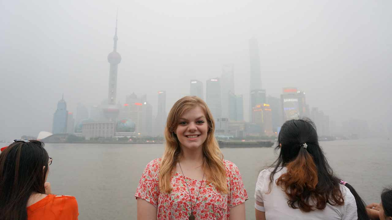 A woman smiles in front of a hazy Shanghai cityscape