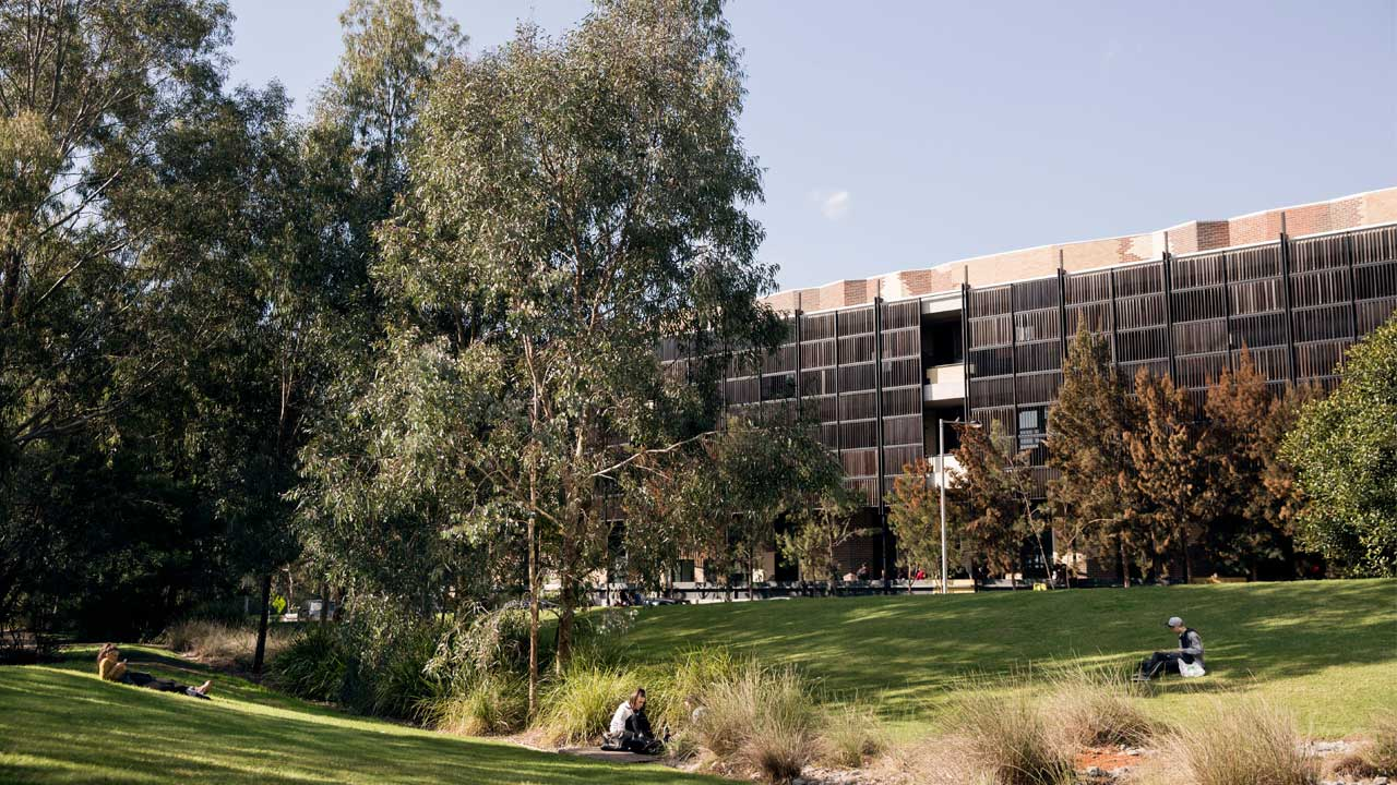Three students scattered across a grassy quad on Deakin's campus study and relax