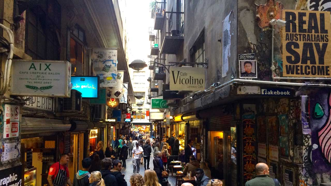 A laneway lined with restaurants and shops in downtown Melbourne is crowded with patrons
