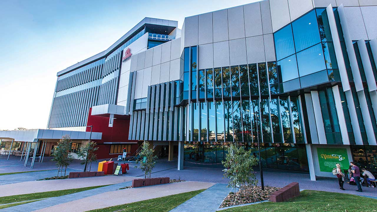 Two buildings on Griffith's Gold Coast campus with windows reflecting the blue sky and trees