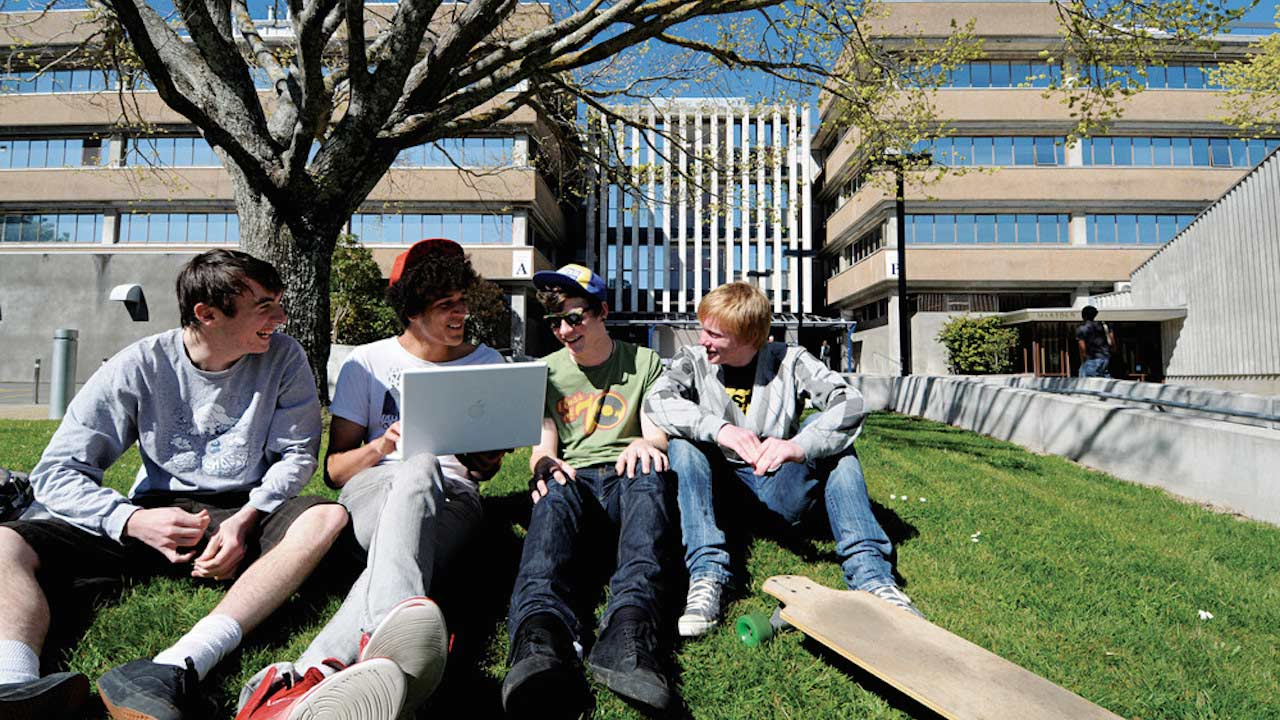 Four boys sit together on the grass talking on Massey University Palmerston North's campus