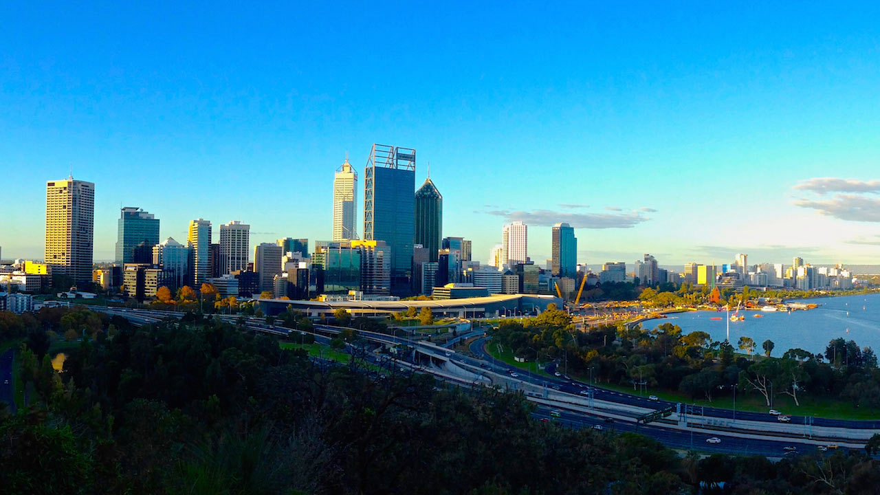 A highway leading to Perth's cityscape against a blue sky
