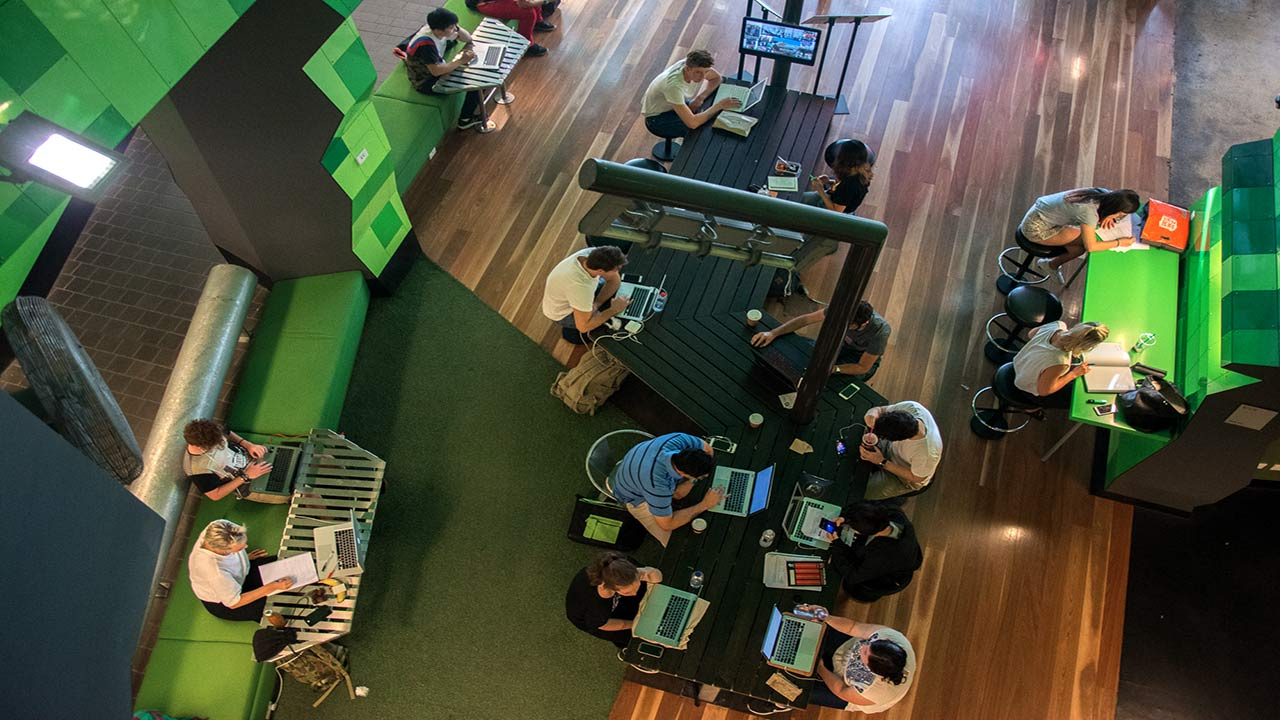 An aerial view of students on their computers or gathered studying at tables in a common area of RMIT's campus