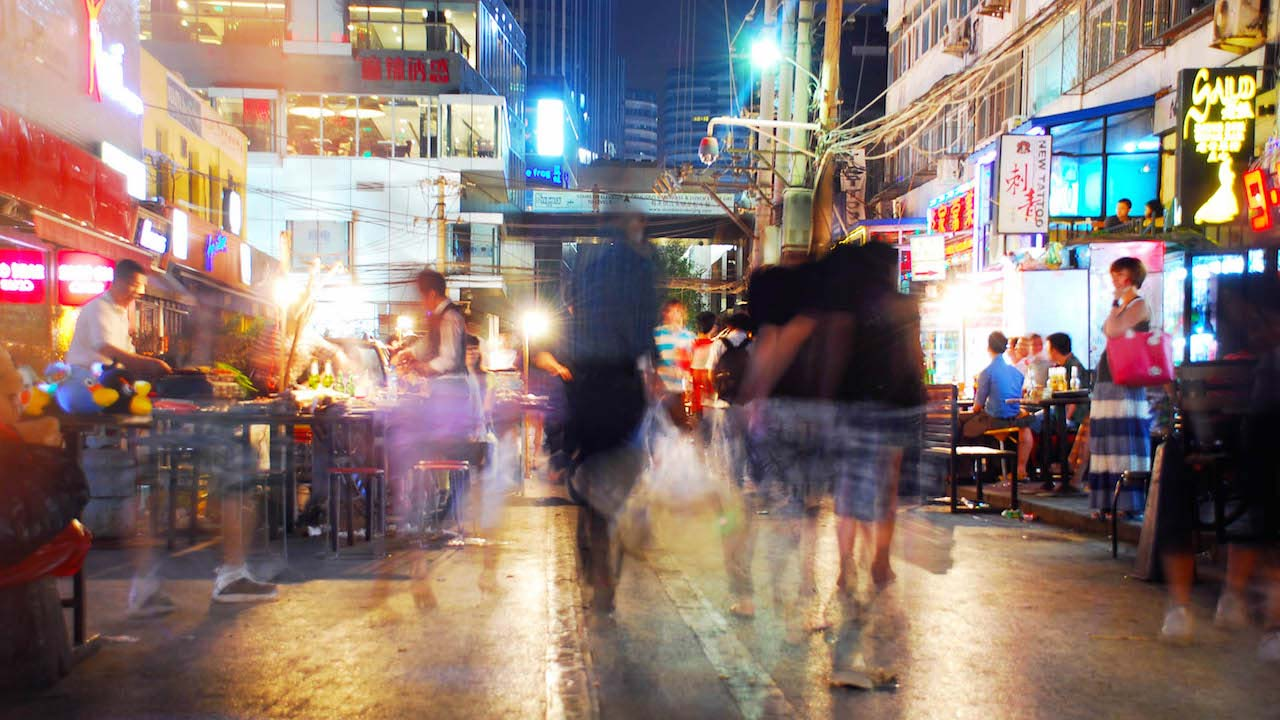 Blurred motion of people walking a brightly lit and bustling street in Shanghai at night