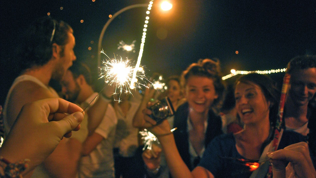 A hand holding a lit sparkler in front of girls' excited faces at nighttime in Thailand