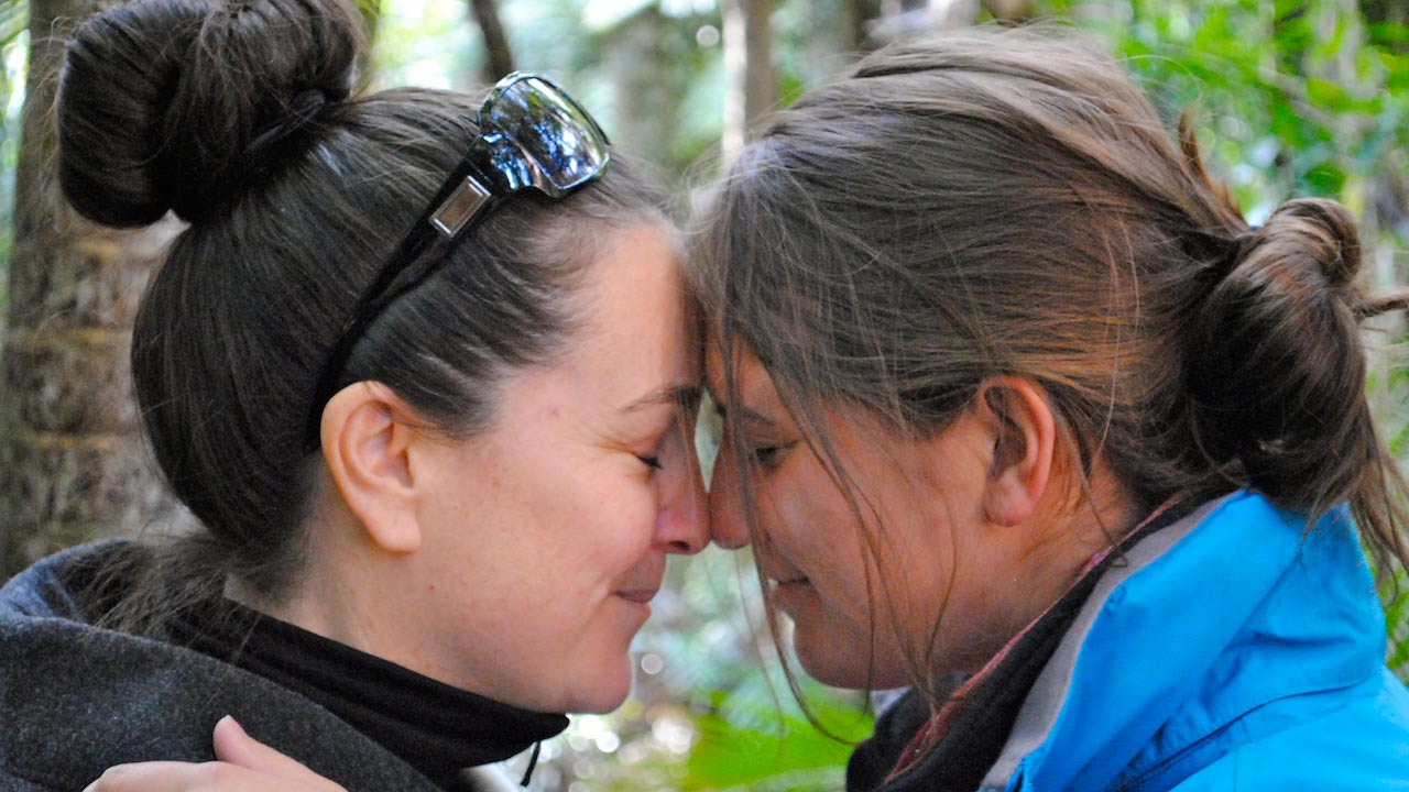 A closeup of two women touching their foreheads together, eyes closed and smiling