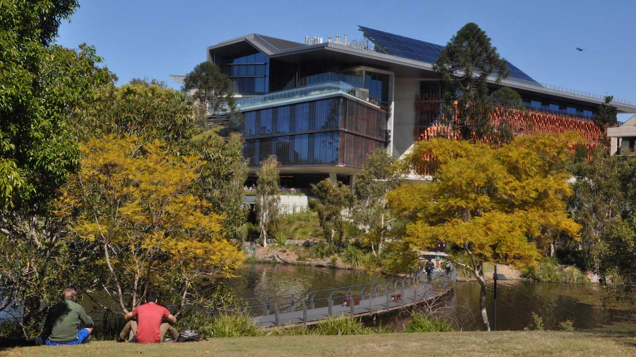 Students sit with their backs to the camera, facing the lake, walkway and building on UQ's campus