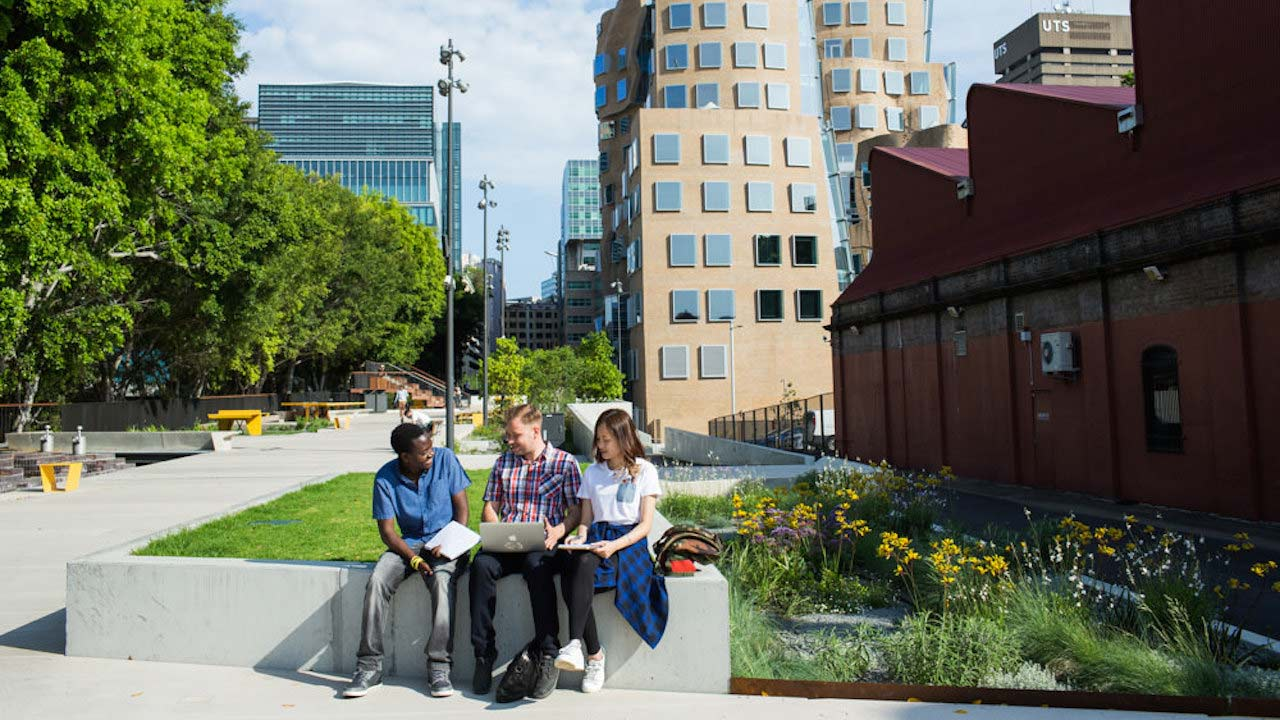 Three people sit chatting on a bench on UTS's campus