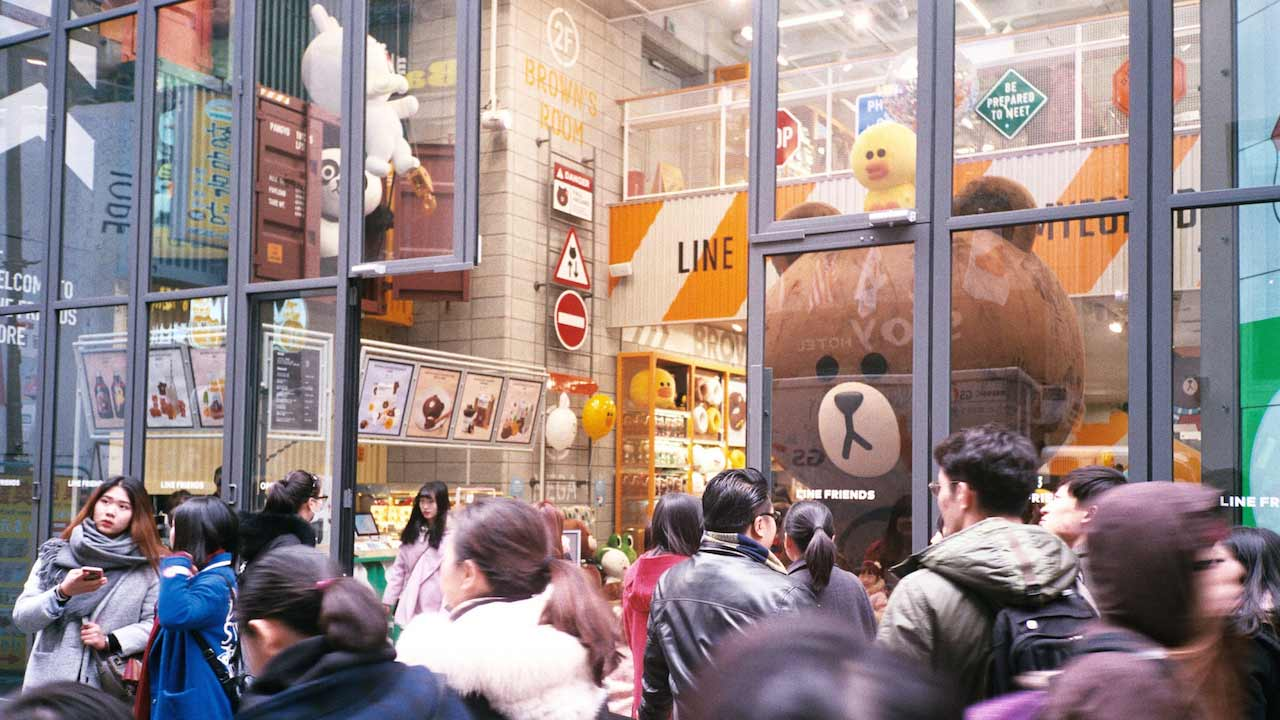 A crowded entrance to a mall with glass windows in Korea