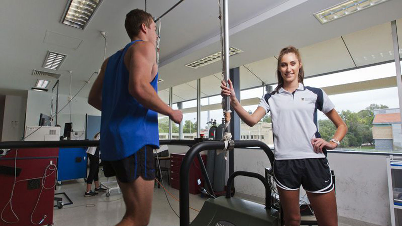 A woman stands smiling next to a man exercising in a classroom at University of Western Australia in Perth