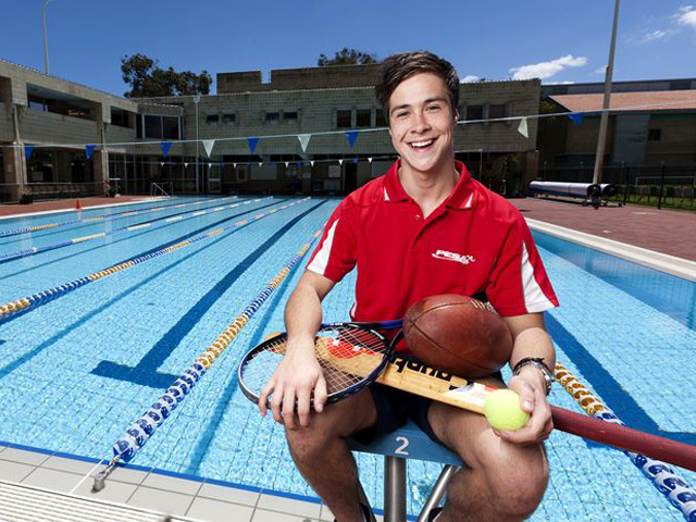 A man sits in front of an outside lap pool holding an array of athletic equipment