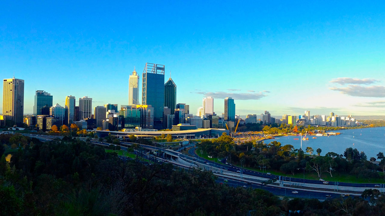 A highway leading to Perth's cityscape with a blue sky above