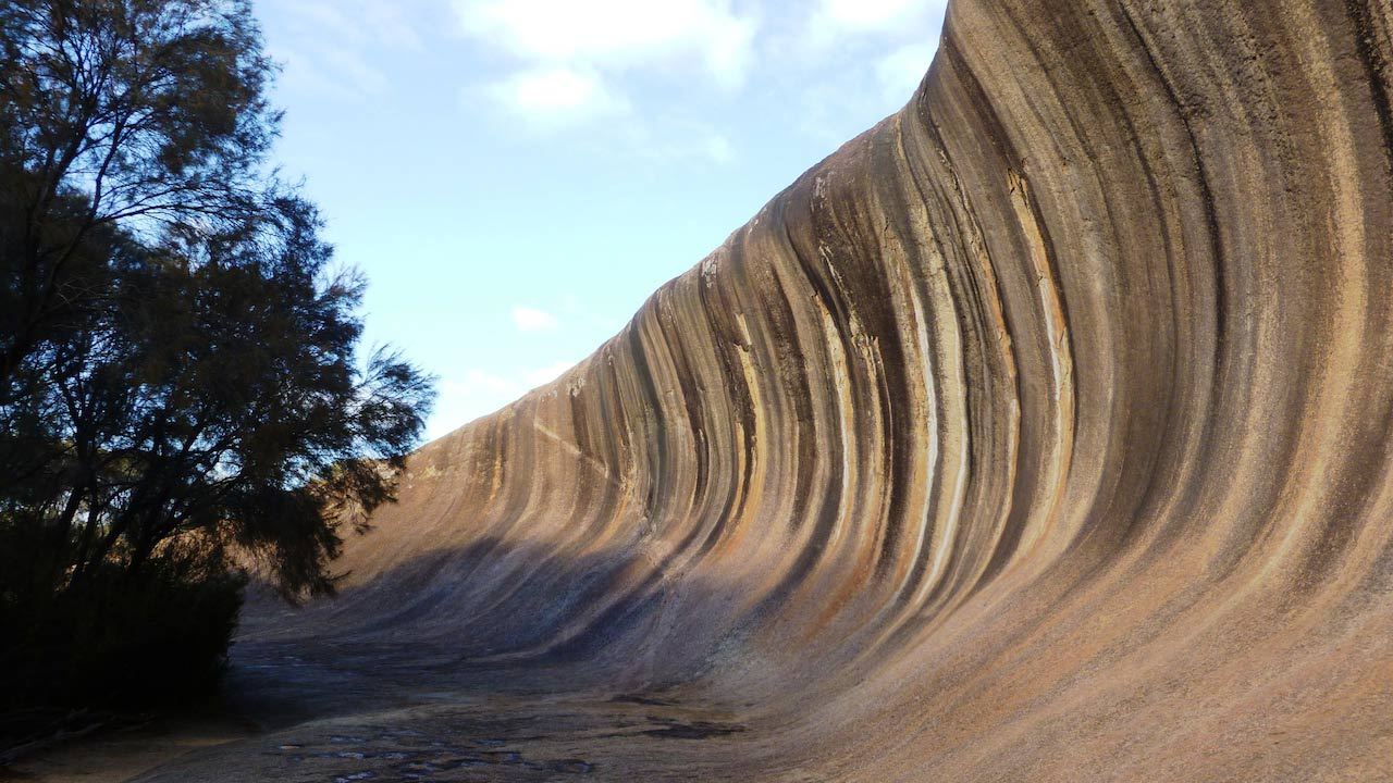 A sand cliff slopes downward below a blue sky near Perth, Australia