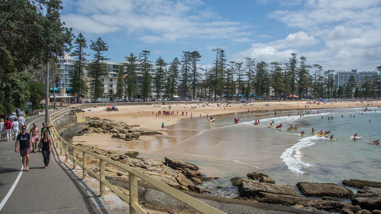 People walk along the pathway that snakes along the shoreline in Manly Beach near Sydney, Australia
