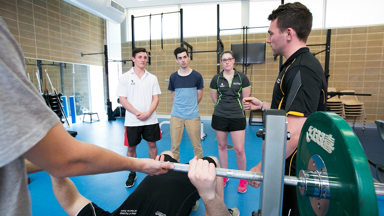 Students observe someone bench pressing in a gym at Murdoch University in Perth, Australia