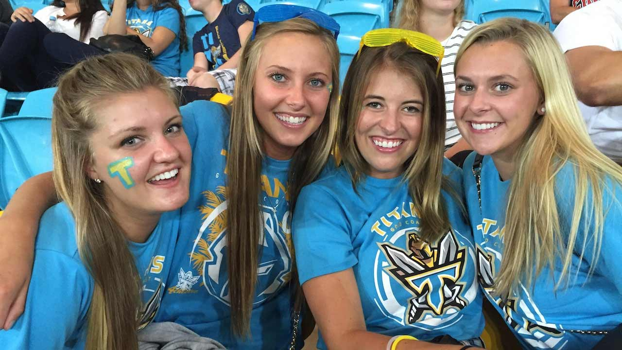 Four women smile together in spirited gear during the Gold Coast Titans Rugby Match